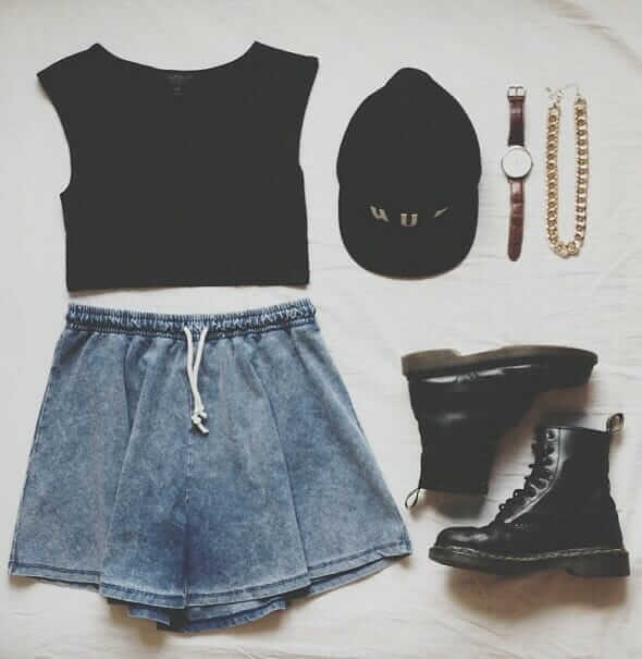 Grunge outfit idea nº9: Black cap, black T, Black Doc Martens, denim print shorts, brown watch, thick banded gold chain necklace