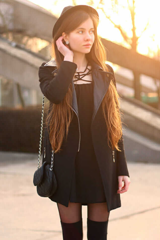 Simple black dress, with a black coat and knee high socks.
