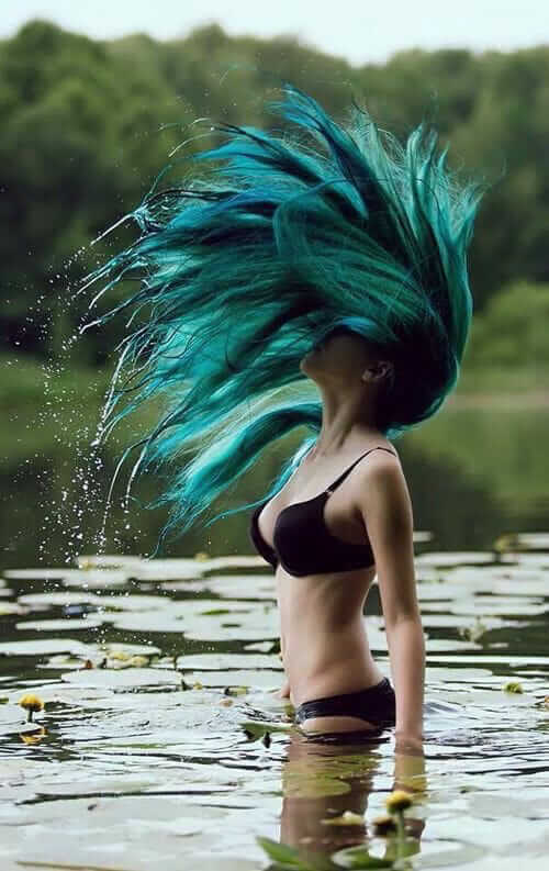 Alternative pale girl with mermaid blue dyed hair with bikini on water